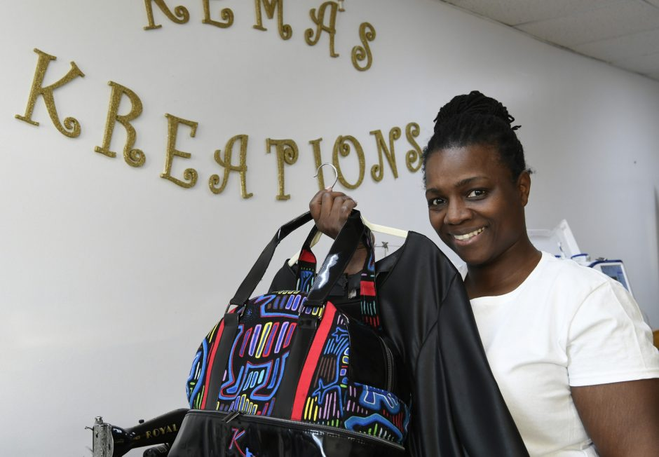 Kema Maxwell owner of Kema Kreations in Albany holds a hand bag and matching dress Thursday, February 14, 2019.