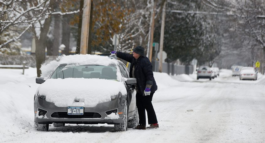 A person clears off snow from their car on Caroline Street in Saratoga Springs Jan. 29