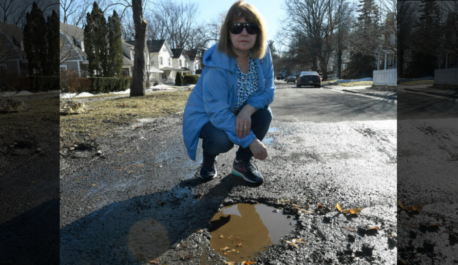 Bette Salisbury in front of one of the many pot holes in front of her of Decamp Avenue home in Schenectady.