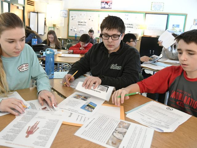 Gowana Middle School students Mirianna Shorkey, Gavin Rueda, and Tommy Quinn review sheets about the dangers of vaping.