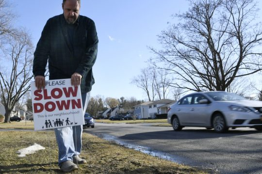 Jeff Smith of Niskayuna puts a sign warning motorists to slow down on his front lawn at Dean and Webster streets on Friday.