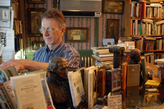 John DeMarco, proprietor of the Lyrical Ballad Bookstore in Saratoga Springs, arranges books at his store in 2006.