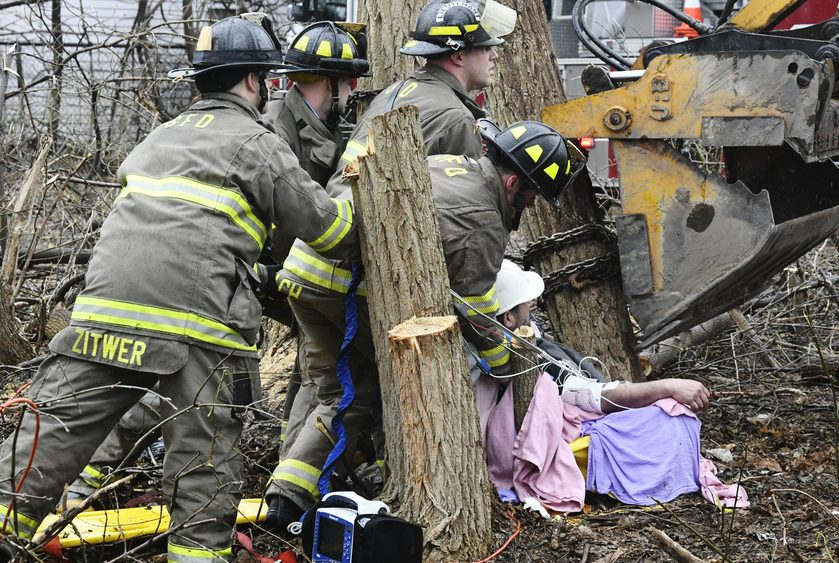 Schenectady firefighters work to free a man's leg after a tree accident behind his residence at 1774 Van Vranken Ave.