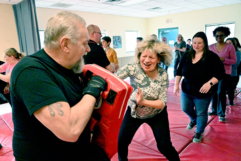 Reporter Karen Bjornland goes into attack mode while Stan Tiska instructs during a self-defense class at the Guilderland YMCA.