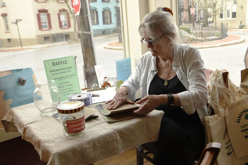 Kat Wolfram prepares brochures promoting the Electric City Cooperative at Arthur's Market in the Stockade last May.