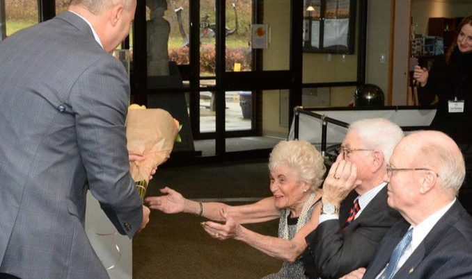 miSci board chairman Tony Farah gives Jane Golub a bouquet of roses in 2016