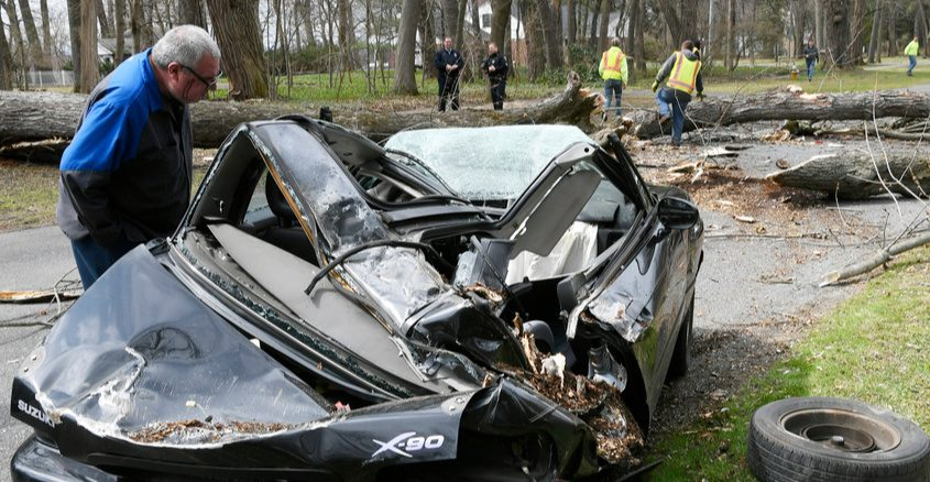 The driver looks over the remains of his car Thursday morning on Sunnyside Road in Scotia