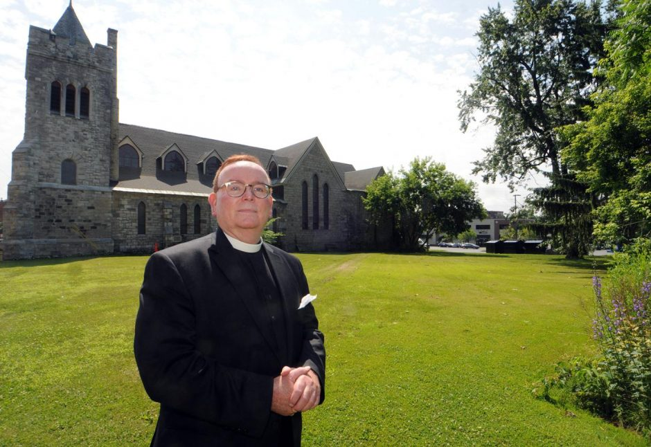 Rev. Marshall J. Vang stands in front of the Bethesda Episcopal Church on Washington Street in Saratoga in 2014.