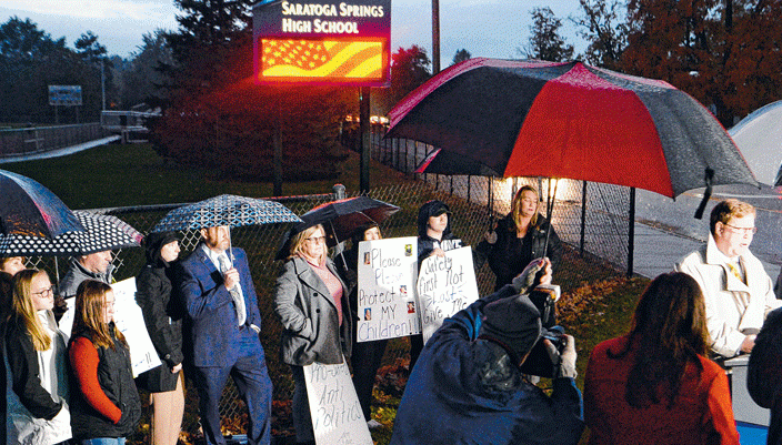 A group that supports arming district grounds monitors rally before the Saratoga City School District Board meeting on Oct. 23.