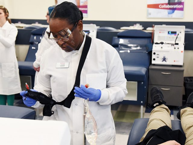 Livina Ross, a phlebotomist with CSL Plasma in Schenectady, works with a new donor at the facility on April 19.