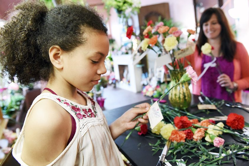 Brooke Fitzpatrick of Northville tapes cards with quotes on carnations at Peck's Flowers. Flowers were handed out to visitors.