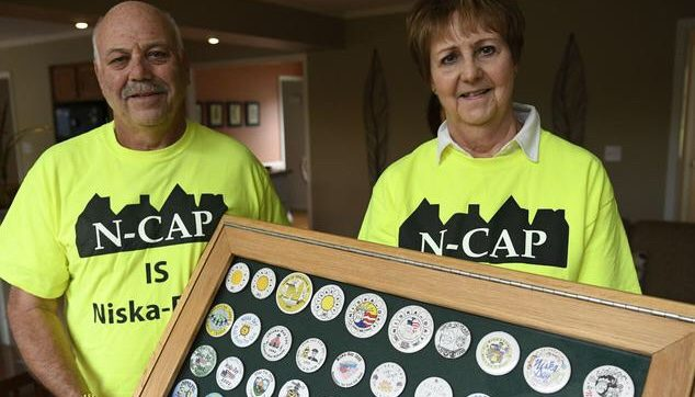 Bill Leader, left, and his wife, Denise, hold a display case filled with Niska-Day pins.