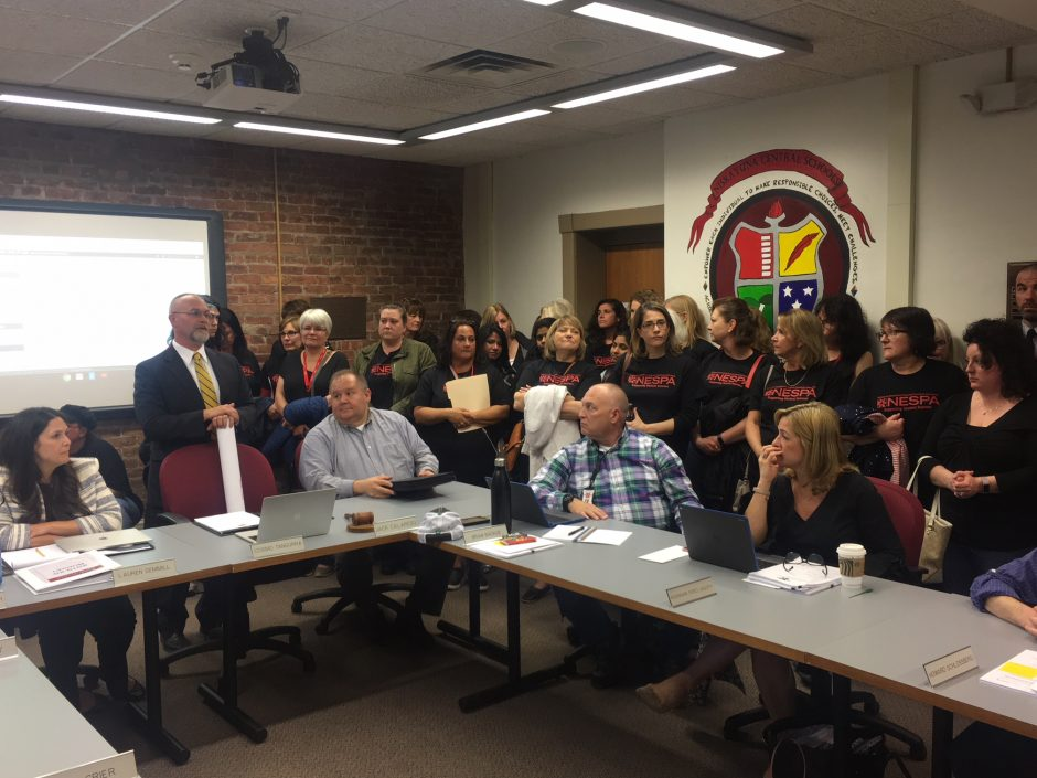 Members of the Niskayuna Educational Support Personnel surround the school board table at a packed meeting Tuesday night.