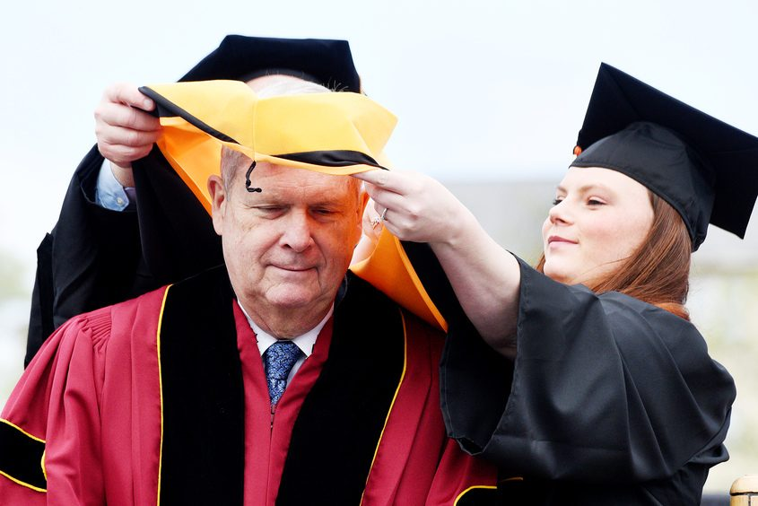 Keynote Speaker Thomas J. Vilsack, has an honorary hood placed on him before addressing SUNY Cobleskill's commencement Saturday.