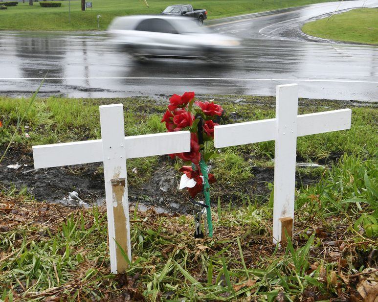 Two white crosses overlook Saturday's crash scene, one for each person killed.