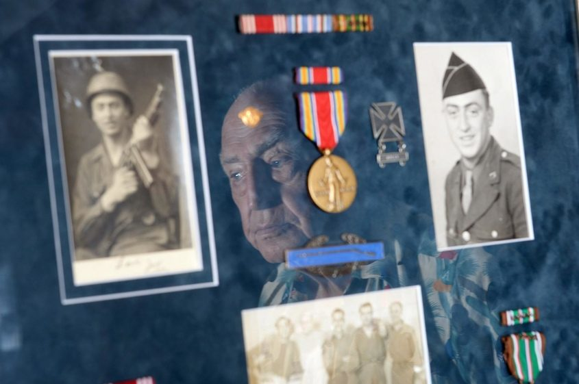 World War II veteran Joseph Ross, who survived deployment at Omaha beach during the D-Day invasion, is reflected in a display.