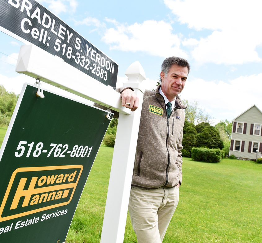 Real Estate agent Bradley Yerdon stands next to a home for sale at 236 County Route 107 in Johnstown.