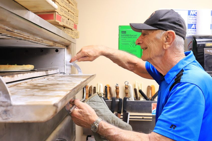 City Mission of Schenectady volunteer Jerry Riggi Jr. checks the crust of a baking pizza in the Mission's kitchen Thursday.