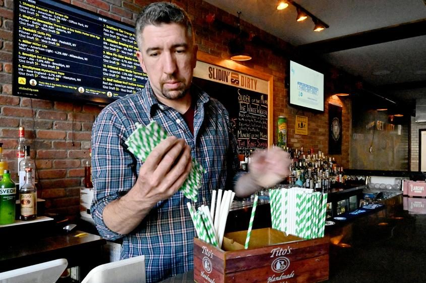 Tim Taney, owner of Slidin' Dirty, located at 512 State St. moves straws at the bar in April