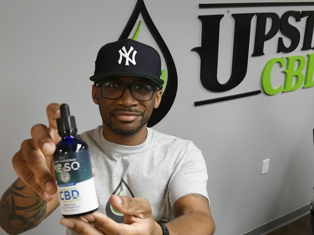 Donald Anderson, owner of Upstate CBD, holds a bottle of product during its official grand opening on June 20.