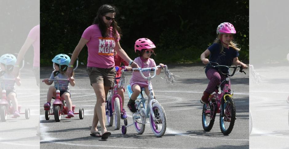 Childeren ride their bicycles on a figure 8 track behind Van Antwerp Elementary School as part of a bike rally.