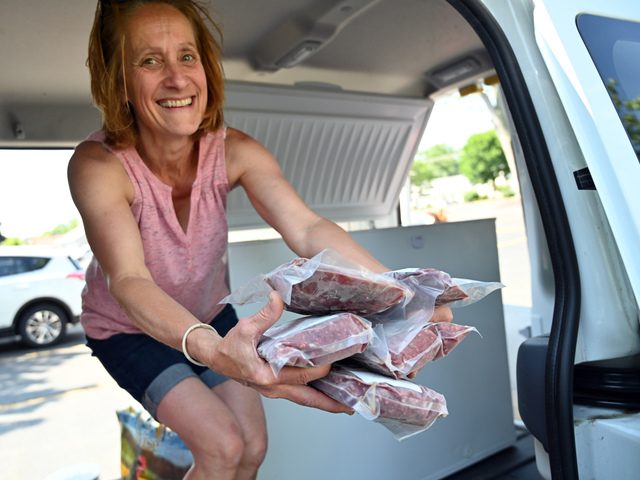 Patty Nally of Charlton pulls steak sandwich meat from the freezer of her van at the swap.