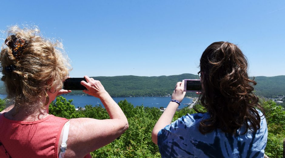 MaryBeth Matthews, of Colonie, and her daughter Laura take photographs of Lake George off Prospect Mountain, June 9, 2019.