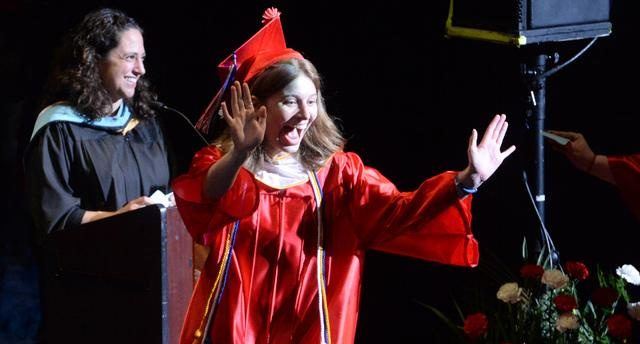 Breanna Burns shows her excitement as she crosses the stage to receive her diploma.