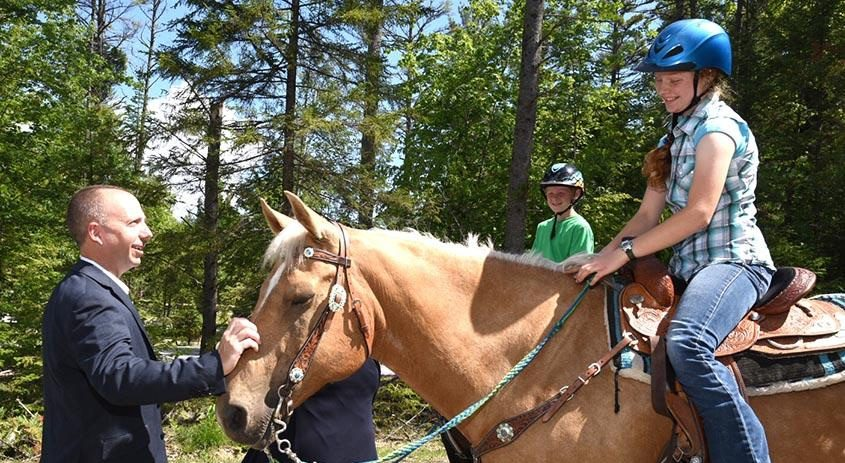 State DEC Commissioner Basil Seggos greets a young equestrian Wednesday at the state's new Frontier Town Campground.