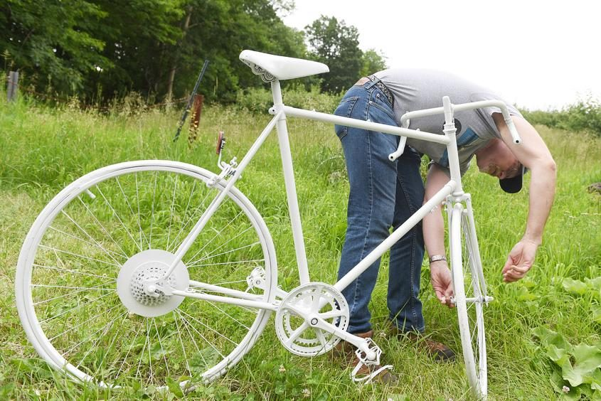 o-organizer David Kraus assembles the new bike at the Dave Ryan Ghost Bike site on Riverview Road.