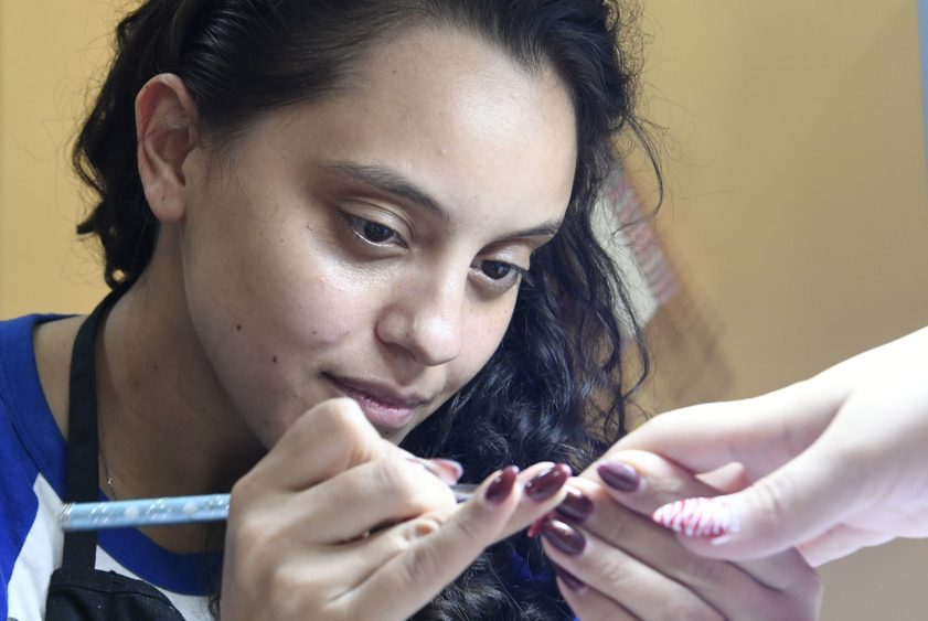 Cussin's Nails owner Cori Rodriguez works on a customer at 118 Jay St. in Schenectady Friday.