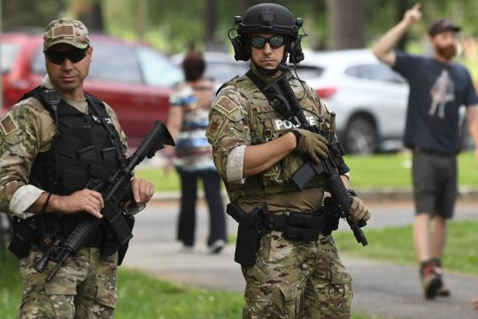 Heavily armed State Park Police officers stand guard before the Phish concert at SPAC Tuesday.