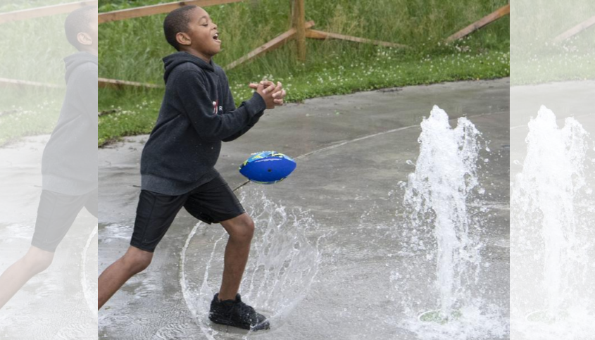 Isaiah Jones, 9, of Schenectady tries to catch a football as he steps onto the splash pad at Tribute Park Saturday.