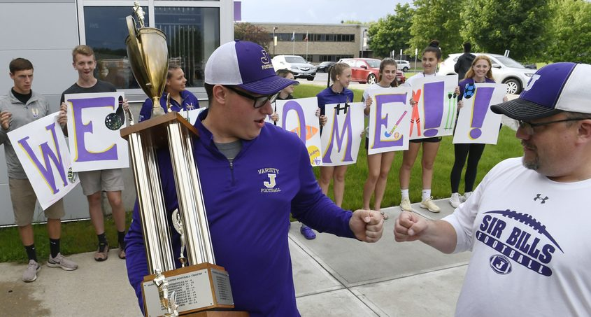 Johnstown High School Jacob Stewart holds the Championship football trophy greets a supporter at a June fundraising rally
