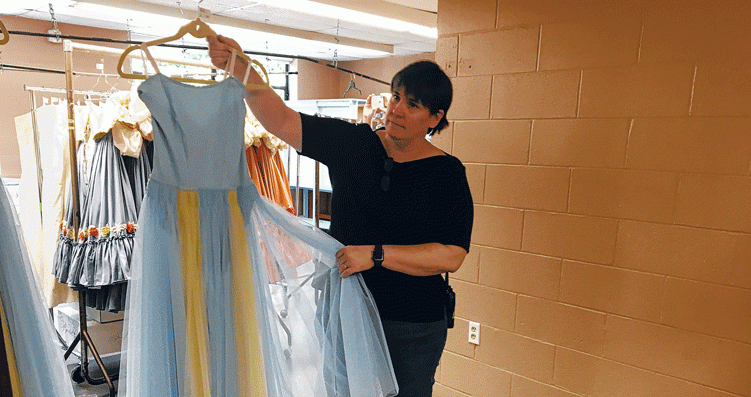 Marquerite Mehler, NYCB's director of production, holds one of the hundreds of costumes that will be worn at SPAC this week.