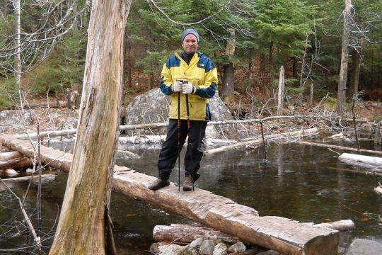 A hiker stops on a log bridge on the trail to Giant Mountain, a High Peak in the Keene Valley region of the Adirondacks.