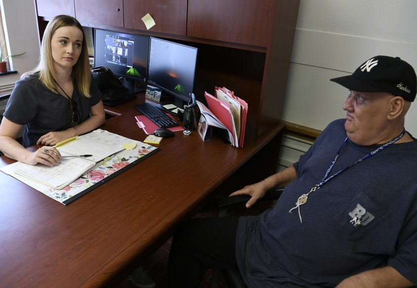 Molly McTernan talks with client Louie Aquasanta at the Bethesda Health Center in Schenectady.
