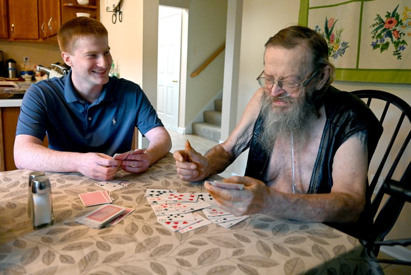 Matthew Cullen, a Union College student volunteers at the Joan Nicole Prince Home, plays cards with resident Bob Humphrey.