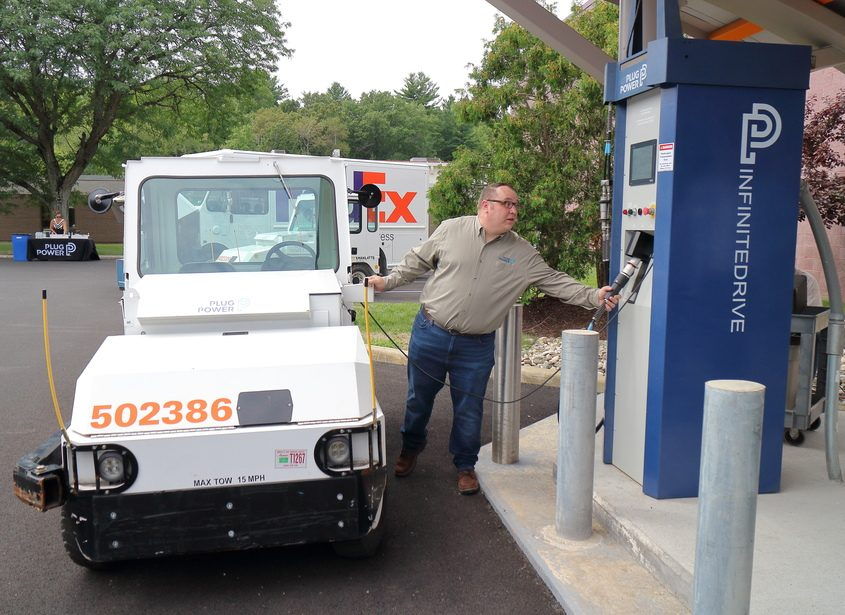 Plug Power systems engineer Rob Tracey refuels a FedEx airport cargo tugger equipped with a Plug Power hyrdrogen fuel cell.