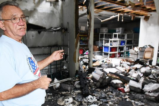 Cliff Seguin, of Operation Adopt A Soldier, stands near the 266 full boxes ready to be sent destroyed in a Saturday fire.
