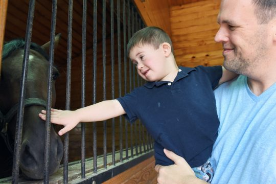 Ryland Miller, 4 of Malta, and his father, Craig, pet Surreal Gentleman at Mill Creek Farm in Saratoga on Sunday.