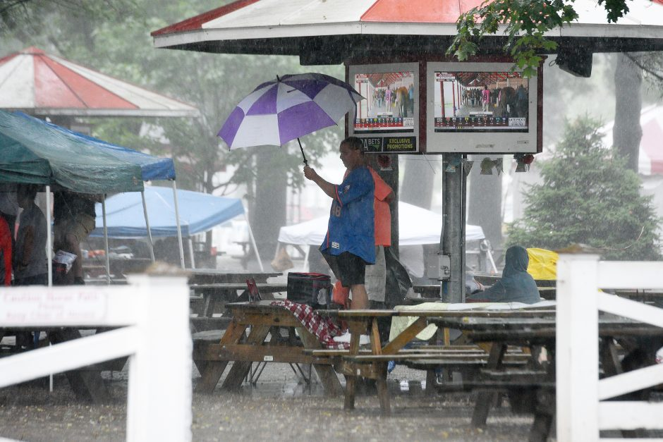 People keep under cover as a storm rolls through at Saratoga Race Course in Saratoga Springs on Wednesday, August 21, 2019.