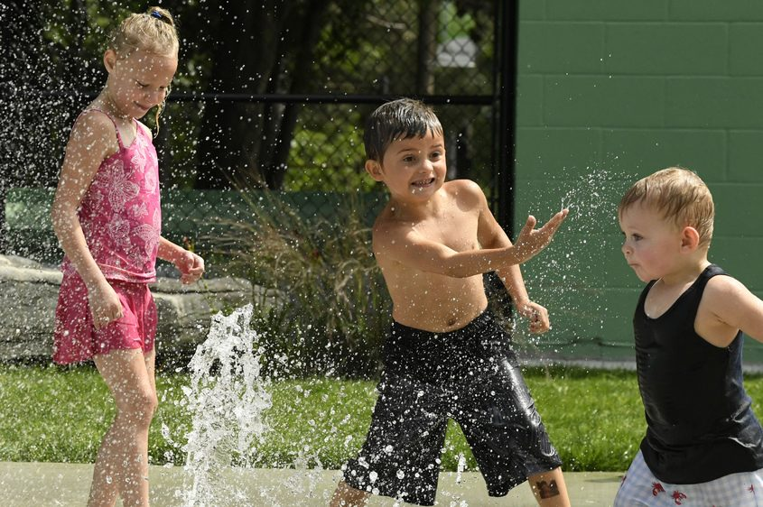 Zeke Carlock, 6, splashes Jackson Rotter, 2, with water as Angelina Tamburrino, 7, looks on at the splash pad in Woodlawn Park.