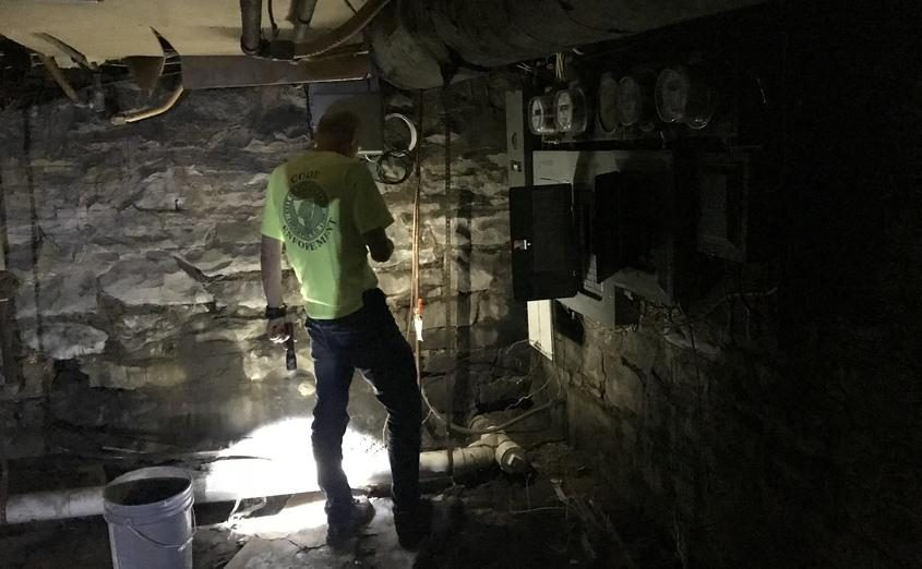 City code inspector Cezary Mazur examines the basement of a State Street apartment building.