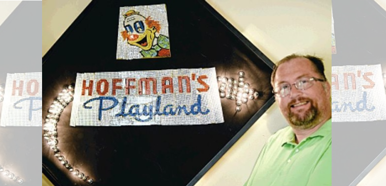 Chuck Miller poses at his Green Island home with his re-creation of the Hoffman's Playland sign.