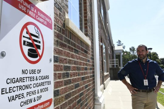 Communication Specialist Matthew Leon looks at a new sign outlining the district's substance-free policy at Van Antwerp.