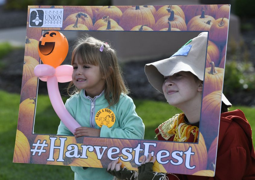 Abby Boardman, 3, has her picture taken with Cecila Bauer, 14, at the annual Upper Union Street Harvest Festival Saturday.