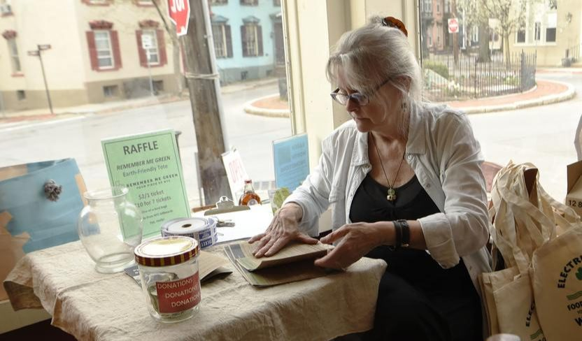 Kat Wolfram prepares brochures promoting the Electric City Cooperative at Arthur's Market in The Stockade last year.
