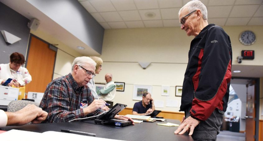 Election inspector Mike Laft helps Ken LaPents sign in during the first early elections at Niskayuna Town Hall, October 26, 2019