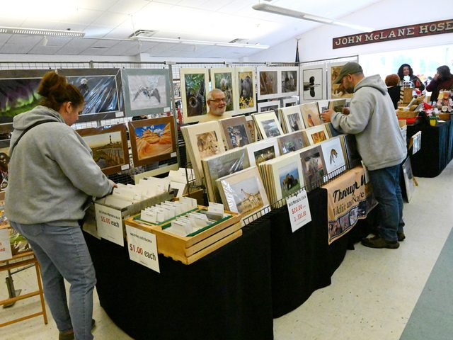 Two shoppers peruse through the selection of photographs by Denny Donohue at the Rexford Fire Department's fall craft fair.